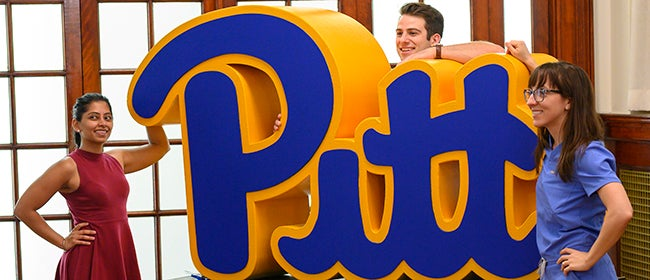three students posing with large 3D Pitt Script logo