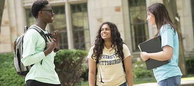 three students talking outside cathedral of learning