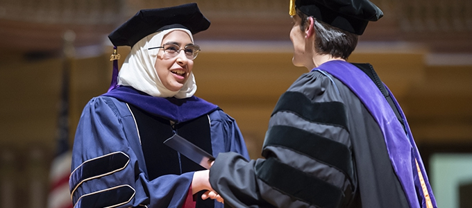 law graduate accepting diploma from dean of school
