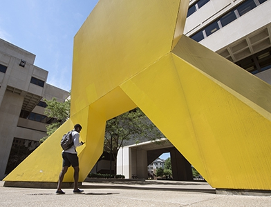 student walking toward large yellow sculpture