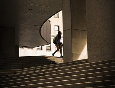 student walking on steps into Pitt Law building