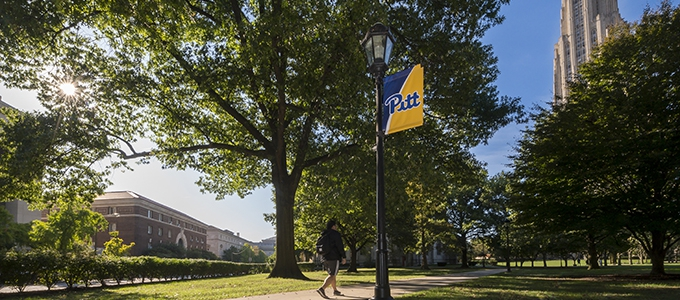 student walking past Pitt banner toward cathedral of learning in fall