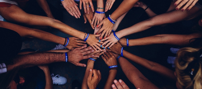 many hands representing different skin tones reaching together