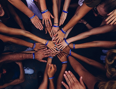 people representing different skin tones gather and reach hands forward together