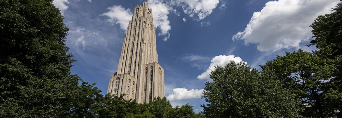 Cathedral of learning against blue sky and fluffy clouds