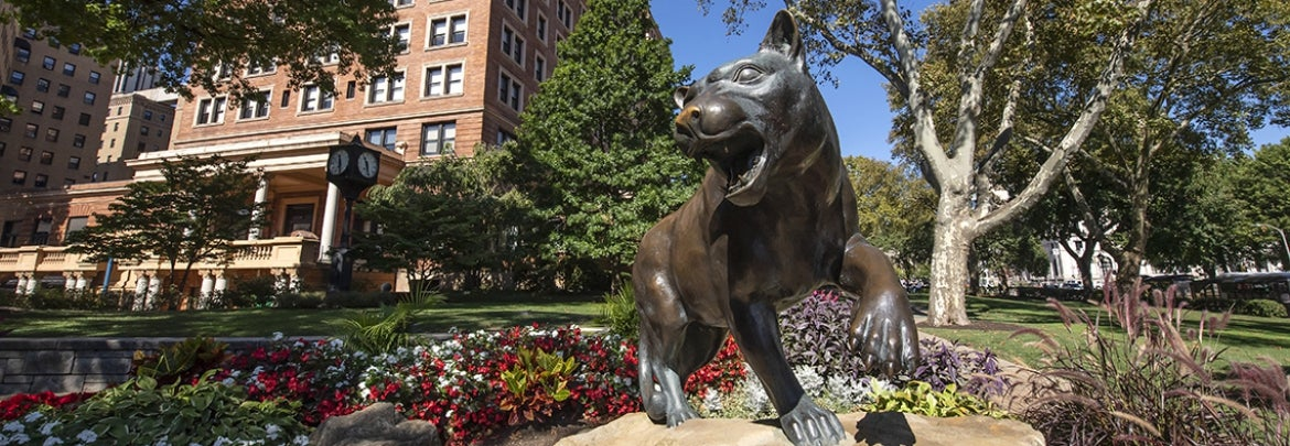 panther statue in front of William Pitt Union with summer flowers