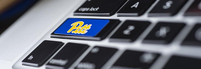 closeup of laptop keyboard with Pitt logo sticker on shift key